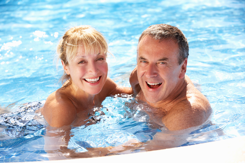 Senior Couple Having Fun In Swimming Pool