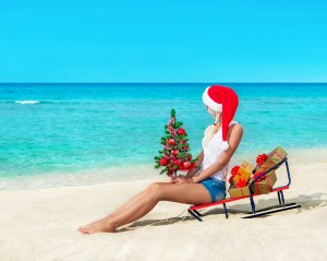 Cute blonde woman at sea beach in santa hat sitting at sled with
